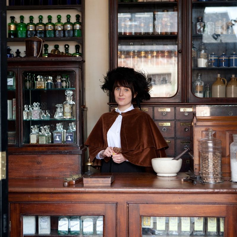 Costumed interpreter dressed in Victorian dress behind the counter in the Chemist shop on the Victorian Street