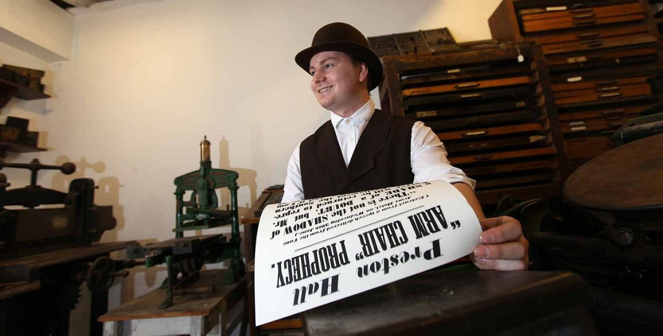 An image of a costumed interpreter holding a newspaper in the printers on the Victorian Street