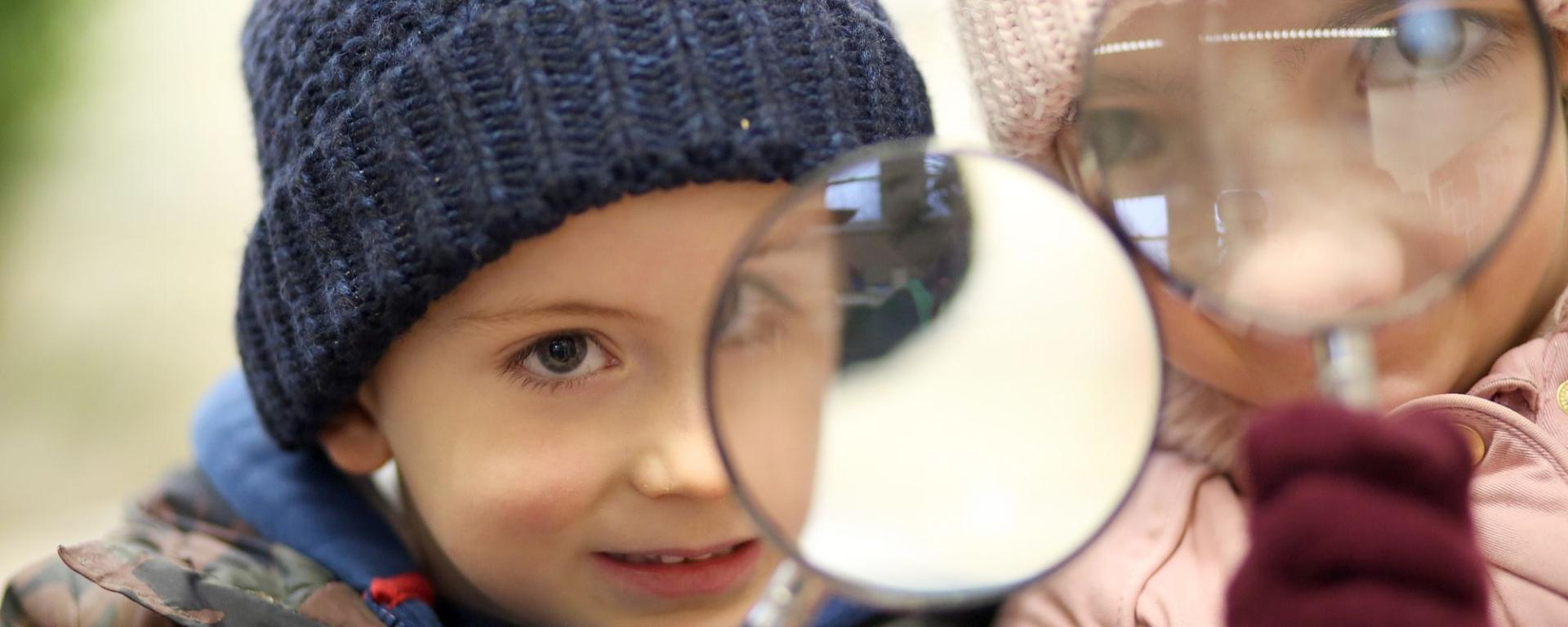 Young Boy And Girl Looking Through A Magnifying Glass