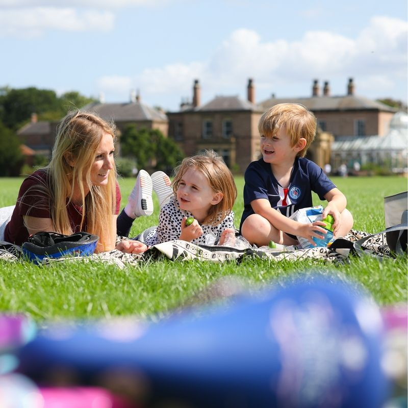 Family Enjoying A Picnic On The Grass In Front Of The Hall