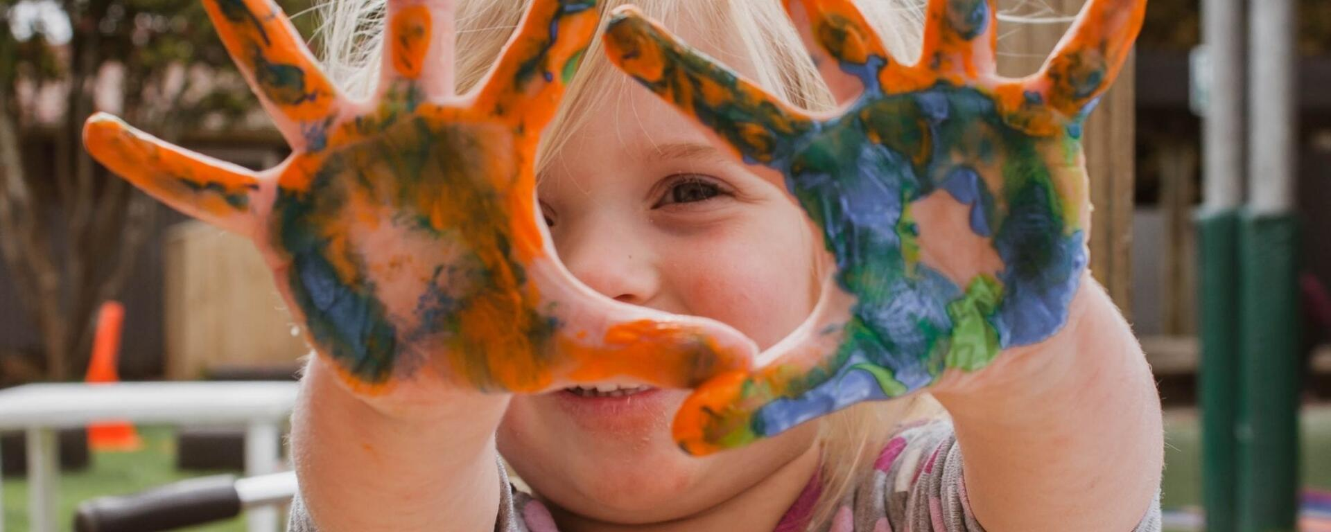 Toddler With Hands Covered In Rainbow Paint